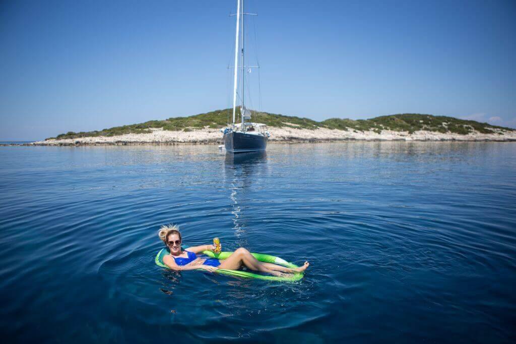 žena v nafukovačke relaxuje okolo jachty