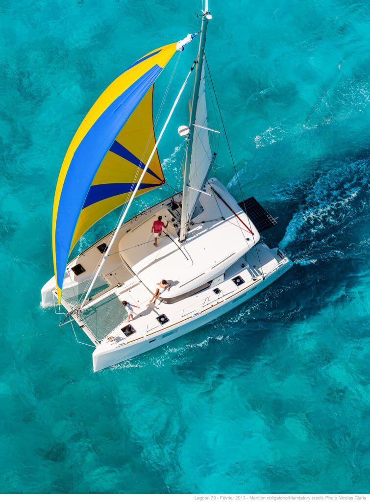 birdeye view of a yacht with colorful sails