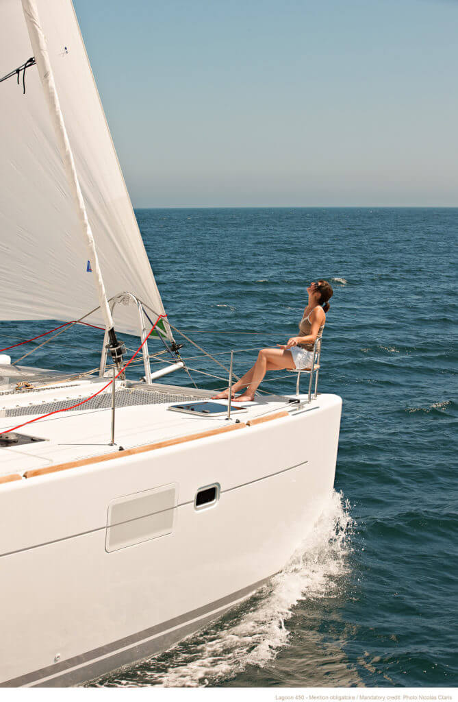 woman sitting in front part of a yacht