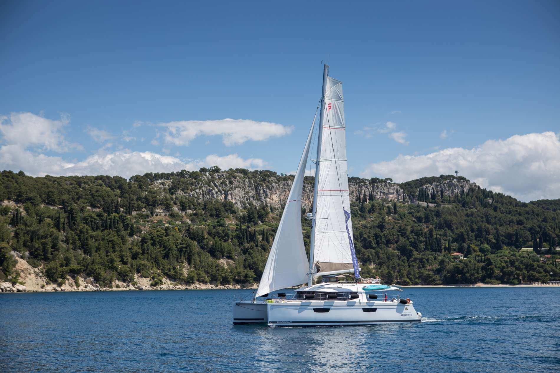 jachta v popredí pobrežného pohoria v Chorvátsku